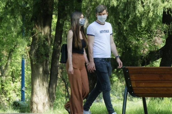 young couple walking in park wearing face masks