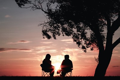 Two people sat outside with a sunrise