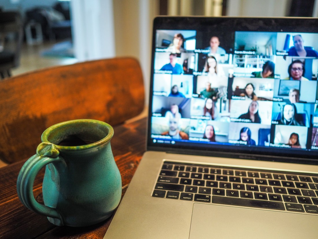Hot drink next to a laptop with group video call