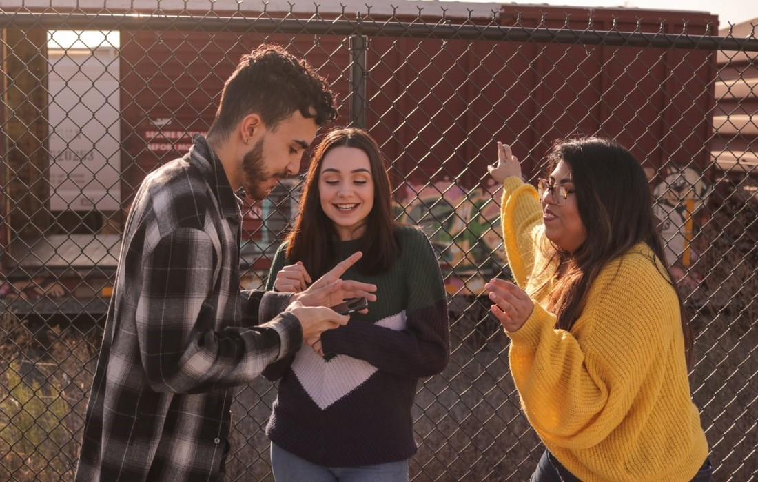 Three young people looking at phone