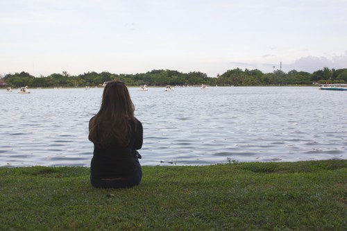Girl sat alone at lake