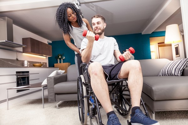 Woman looking at a man in wheelchair doing arm weights