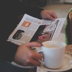 Person holding newspaper and mug of coffee