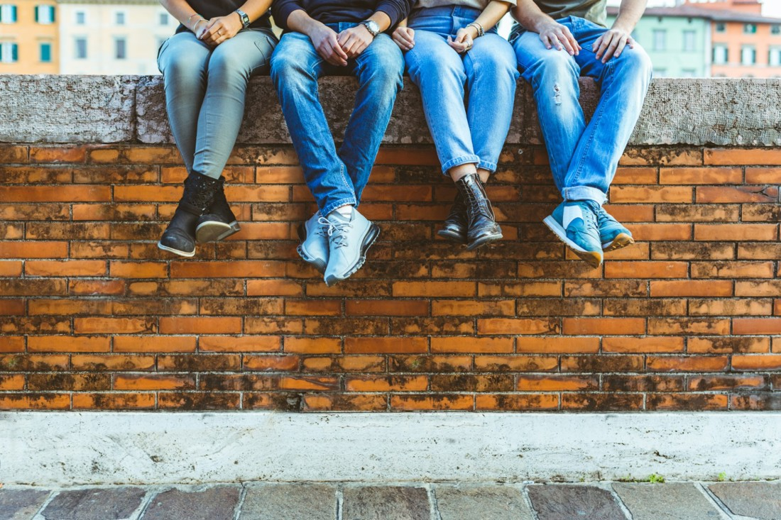 Four young people sat on a wall