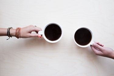Two mugs of coffee being held